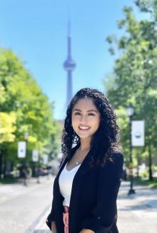 Priyanka Kuugamoorthy - BOD bio pic standing in downtown Toronto in front of CN Tower in background